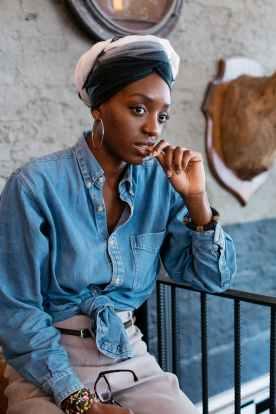 woman wearing denim jacket sitting beside metal railings