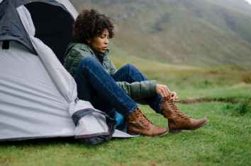 woman sitting on gray tent tying shoe lace